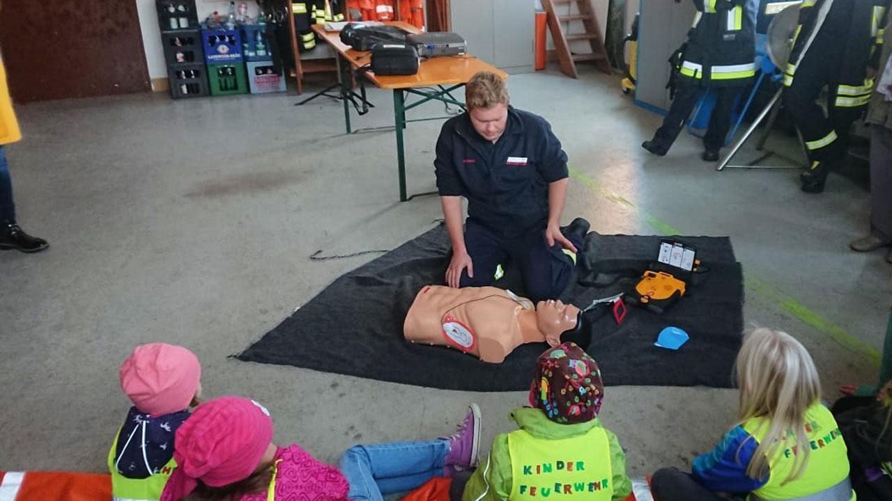 mehrere Personen und Kinder stehen im Halbkreis um eine Reanimationspuppe