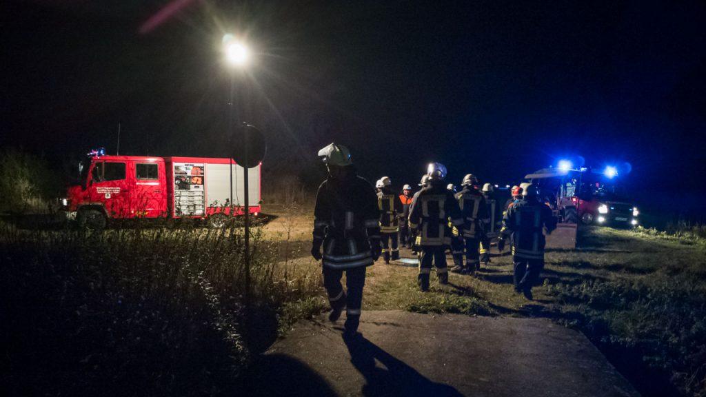Eine Gruppe von Feuerwehrleuten steht nachts neben zwei Feuerwehrautos an der Wörnitz