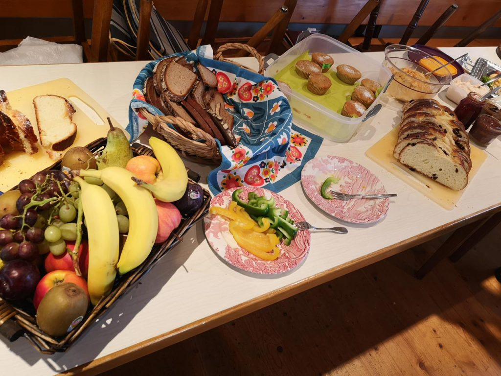 Eine gedeckte Frühstückstafel mit Obst, Kuchen und Brot