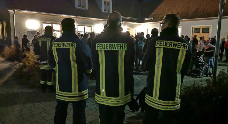 Bild: drei Feuerwehrmänner nebeneinander gezeigt von hinten