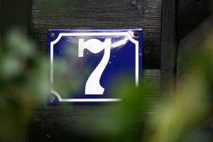 Ein Hausnummernschild hinter Büschen - schlecht zu sehen für die Feuerwehr