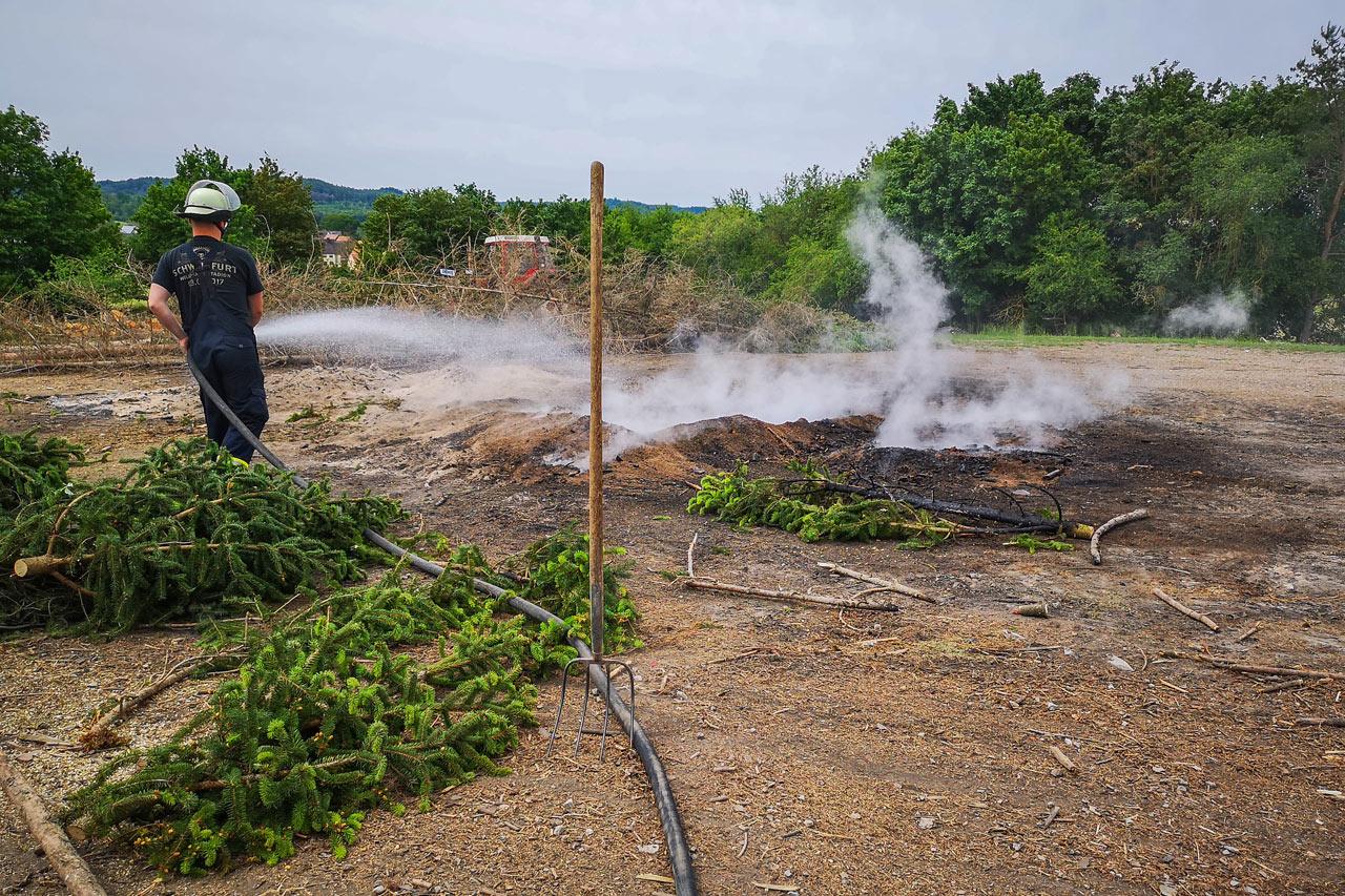 Feuerwehrmann löscht rauchenden Haufen