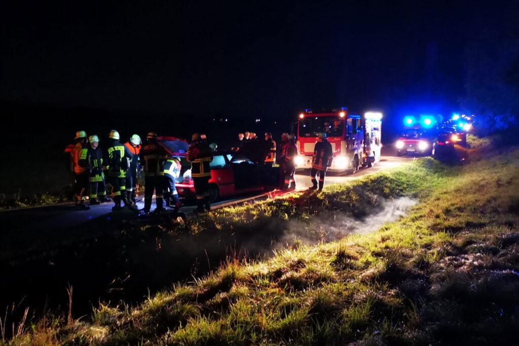 Feuerwehrkräfte stehen um das Auto - im Hintergrund Blaulicht