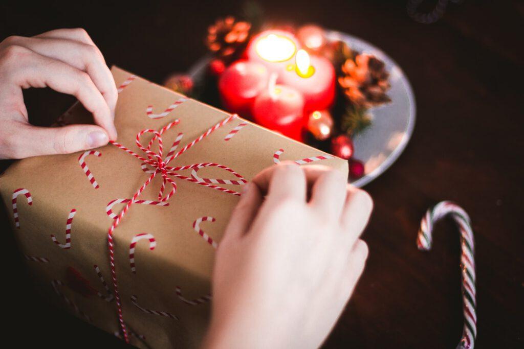 Person packt Geschenk ein - im Hintergrund ein brennender Adventskranz