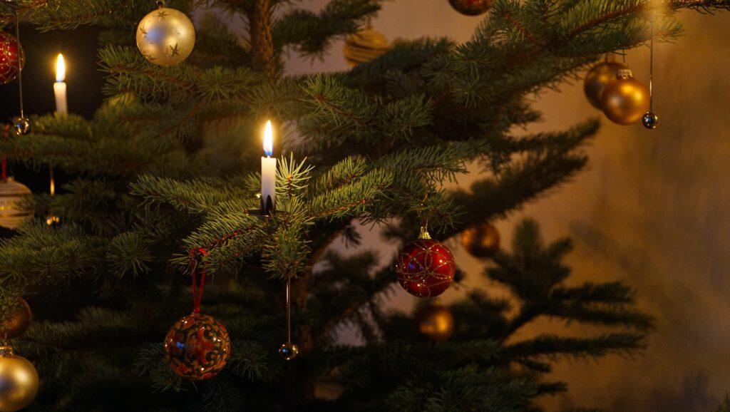 Ein Weihnachtsbaum mit Kerzen im dunklen Zimmer