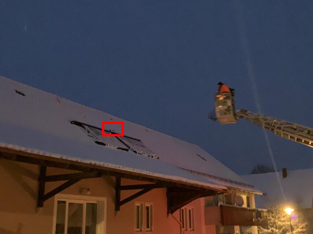 Drehleiter steuert auf Dach mit Schnee zu - klein die Katze im Bild